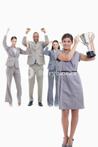 Woman holding up a cup with happy coworkers