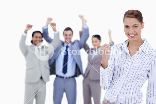 Secretary smiling and clenching her fist with enthusiastic business people