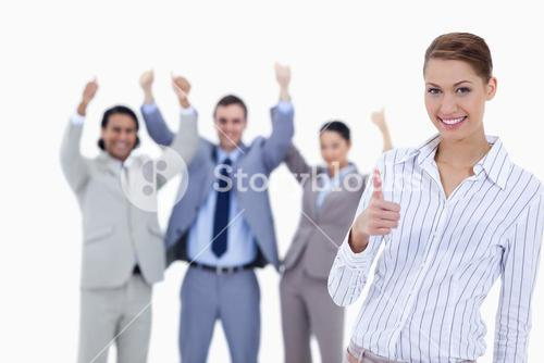 Close up of a woman smiling and approving with enthusiastic business people