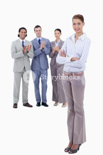 Woman crossing her arms with business people applauding while watching her