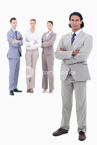 Businessman crossing his arms with serious people in background