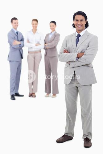 Businessman smiling and crossing his arms with happy people behind him