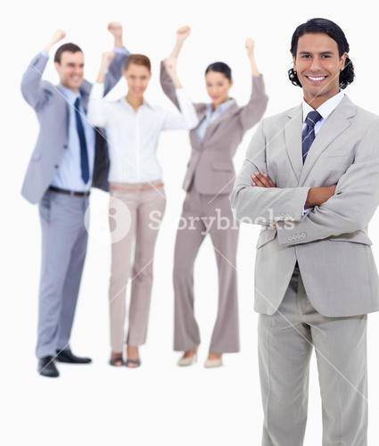 Businessman smiling and crossing his arms with enthusiastic people behind him