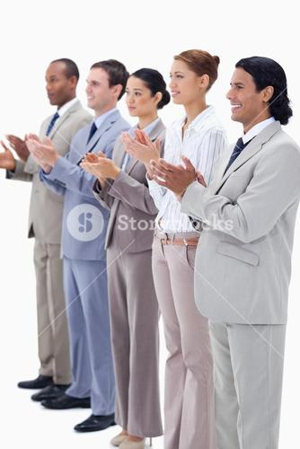 People dressed in suits smiling and applauding