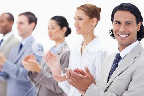 Close up of a business team smiling and applauding