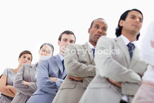 Lowangle shot of people dressed in suits crossing their arms in a single line