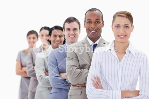 Close up of smiling colleagues dressed in suits crossing their arms in a single line