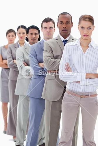 Serious workmates dressed in suits crossing their arms in a single line