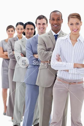 Smiling workmates dressed in suits crossing their arms in a single line
