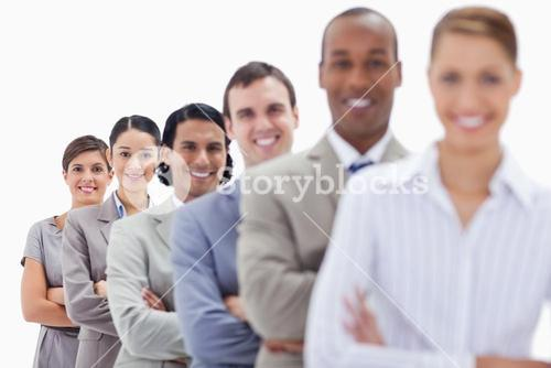 Close up of smiling workmates dressed in suits crossing their arms in a single line