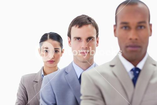 Big Close up of serious colleagues in a single line looking straight