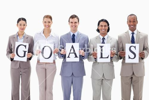 Happy business team holding the letters of GOALS