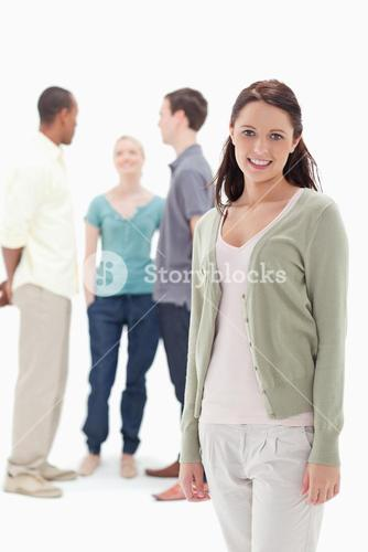 Woman smiling with her friends chatting behind her