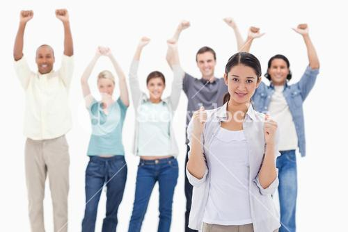 Woman clenching her fists with people raising their arms