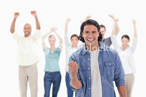 Man clenching his hand with people raising their arms