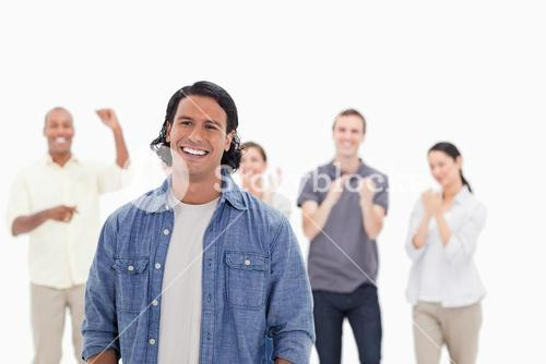 Man laughing with people applauding in background