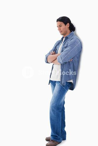 Man crossing his arms looking down and leaning against a wall
