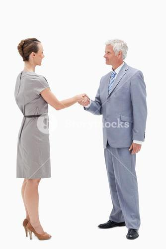 White hair businessman face to face and shaking hands with a woman