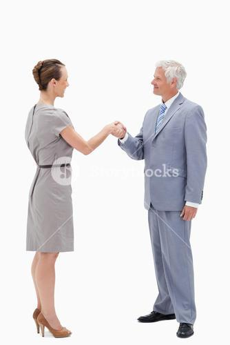 White hair businessman smiling face to face and shaking hands with a woman