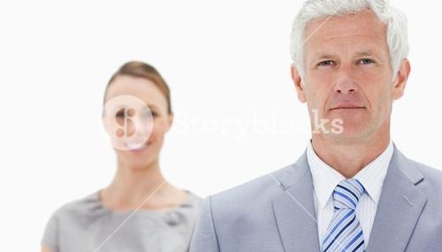 Close up of a serious white hair businessman with a woman smiling behind him