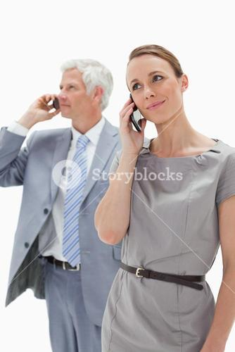 Close up of a woman making a call with a white hair businessman