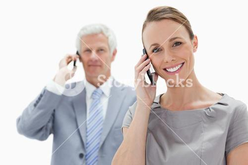 Smiling business people talking on mobile phone
