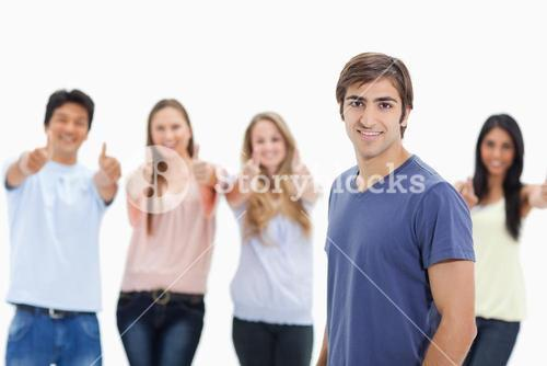 Man smiling with people approving behind him