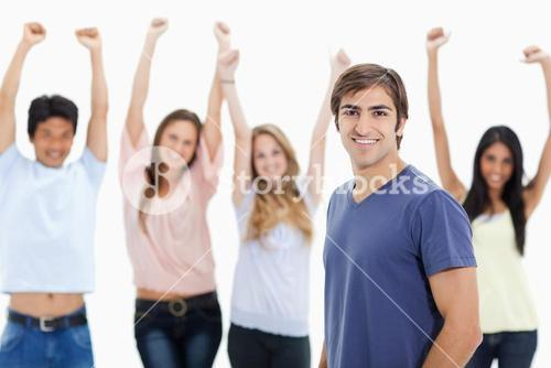 Smiling man with people behind him raising their arms