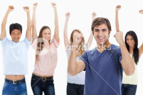 Man clenching his fists with people behind him raising their arms