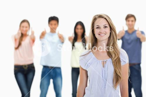 Close up of woman smiling with people approving behind her