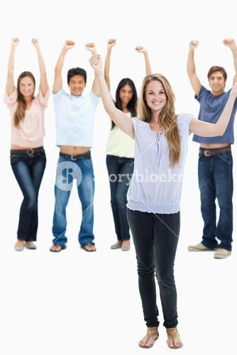 People in jeans with their arms raised