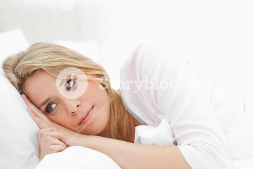 Woman resting in bed eyes open and glancing just ahead of her