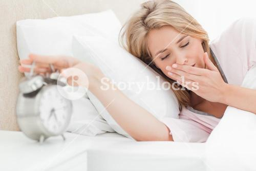 Woman with her eyes closed is reaching to silence her alarm clock