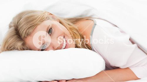 Woman lying in bed, her head on the pillow and eyes open while smiling