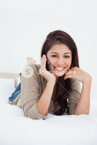 Close up, woman making a phonecall on the bed and smiling as she looks forward