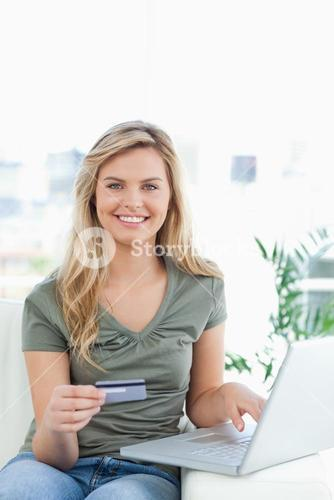 Woman using her credit card and laptop on the couch while smiling