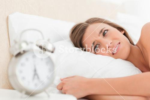 Woman looking agitated by her alarm clock