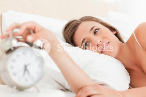 Woman silencing her alarm clock with her hand