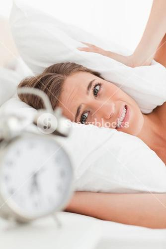 Close up of woman with pillow over her ears