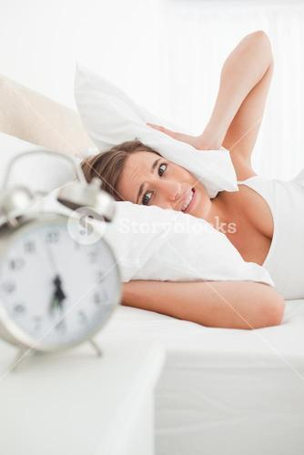 Woman covers her ears with a pillow and looks at her clock in annoyance