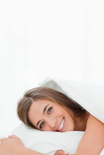 Vertical shot, woman in bed, awake, smiling while looking ahead