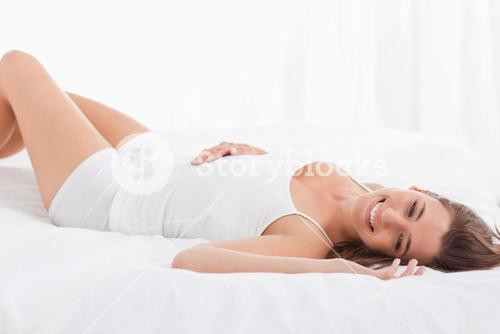 Woman smiling, lying on the bed on her back