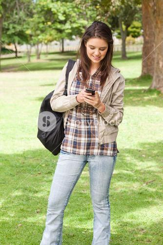 Young student standing while using a smartphone