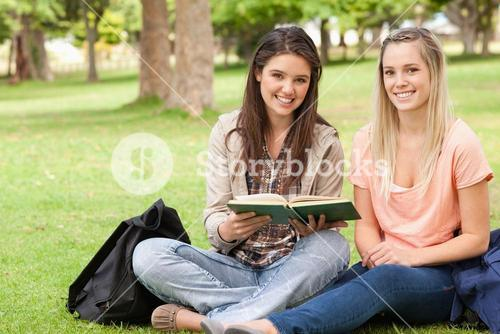 Female teenagers sitting with a textbook