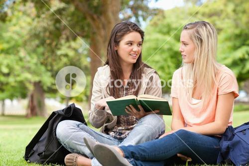 Female teenagers sitting while studying with a textbook