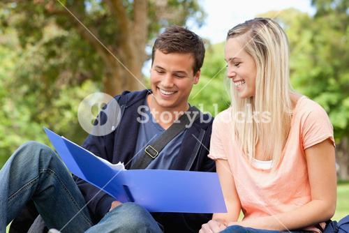 Close up of a smiling tutor helping a teenager to revise