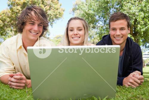 Three smiling students in a park