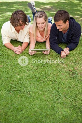 Three young people using a tactile tablet