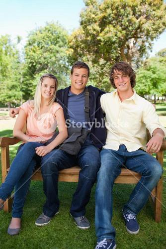 Three smiling students on a bench