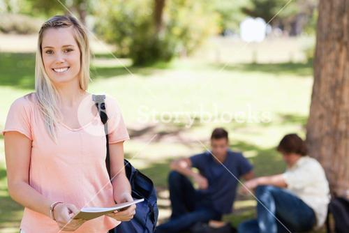 Portrait of a female student smiling while holding a textbook